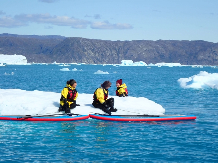 Women taking a break from stand up paddleboarding on an iceberg. Photo by Nuuk Adventure