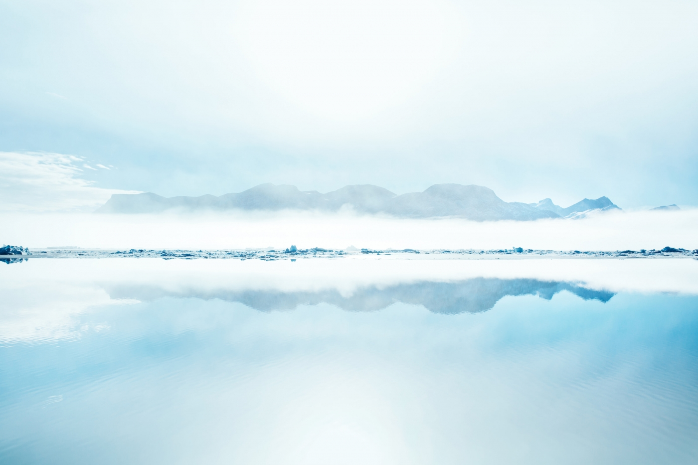 Mountains and fog being mirrored on clear water in the Nuuk fjord in Greenland. Photo by Rebecca Gustafsson - Visit Greenland
