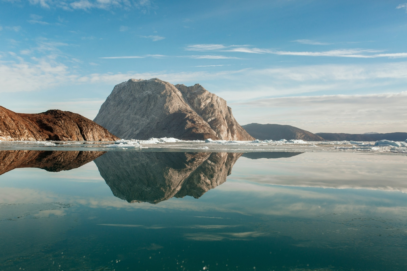 Mountains being reflected perfectly on clear water in the Nuuk fjord in Greenland. Photo by Rebecca Gustafsson - Visit Greenland