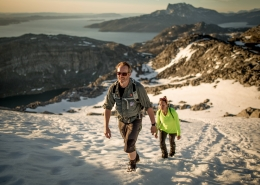 Two hikers on a slope of summer snow ascending Ukkusissaq - Store Malene outside Nuuk in Greenland. By Mads Pihl
