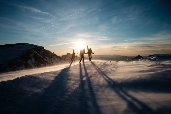Skiers on the summit of a mountain with the sun setting. Photo by Joris Berthelot