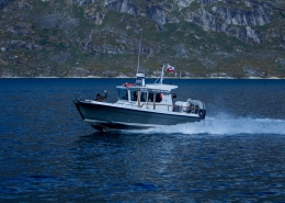 "Qajaq Seaway charter boat ""Arnarulunnguaq"" with passenger standing at the front waving. Photo by Qajaq Seaway"