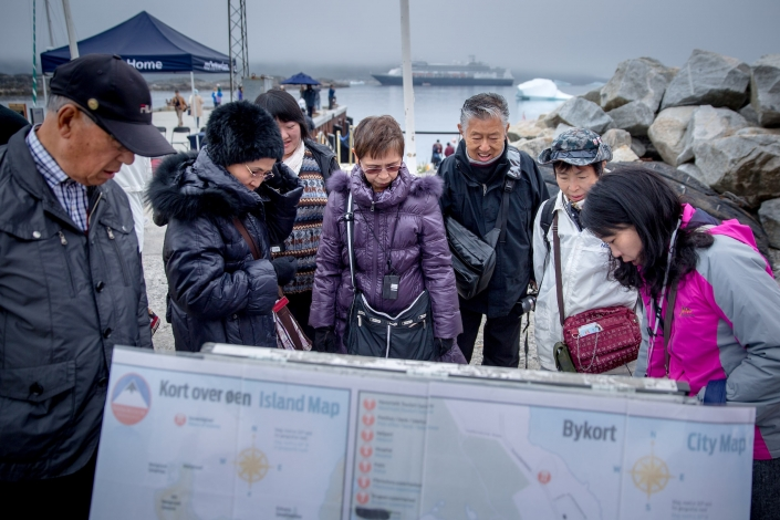 Cruise guests in Nanortalik in South Greenland studying a map of town. Photo by Photo by Mads Pihl - Visit Greenland