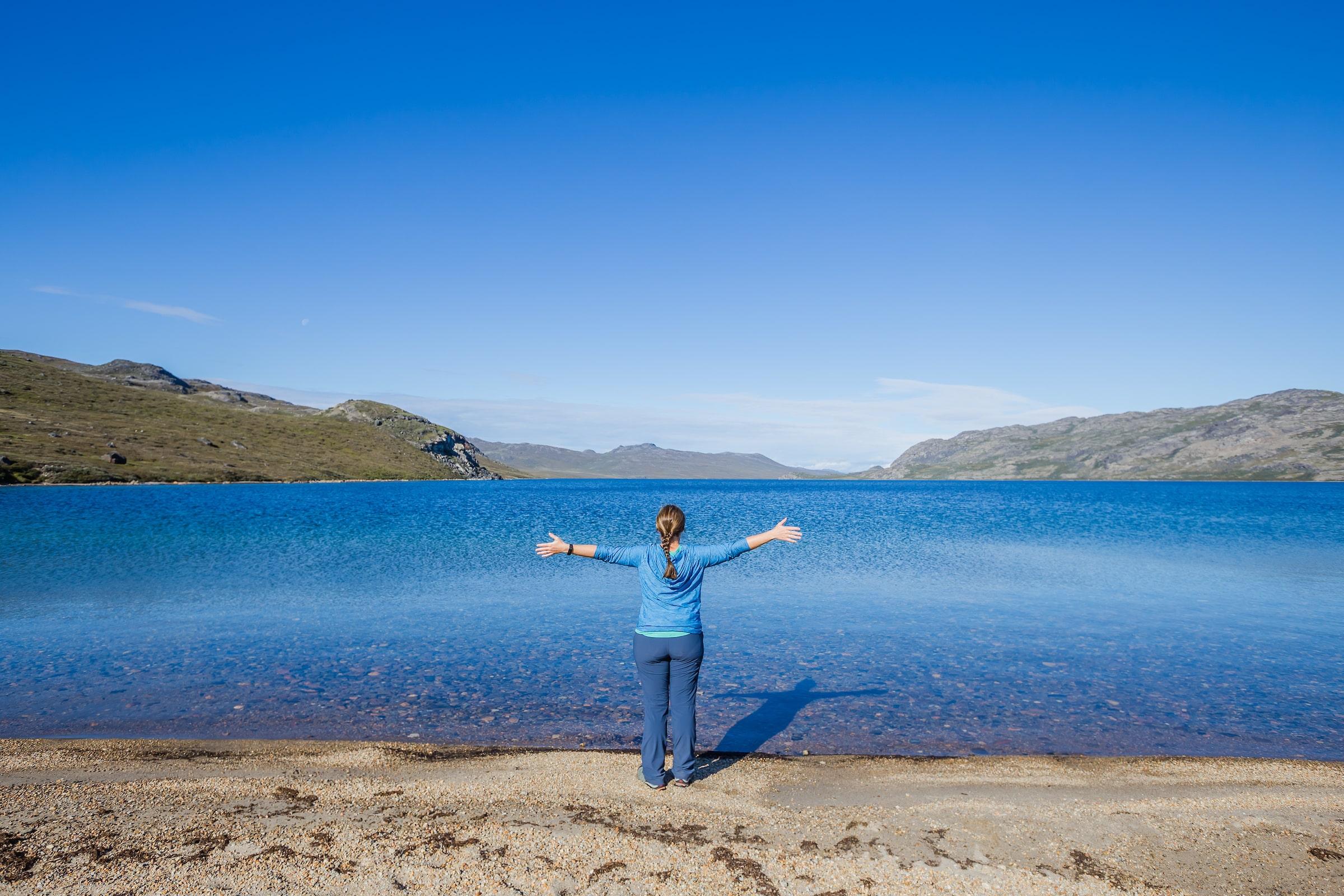 Female hiker enjoying the scenery at Amitsorsuaq Lake along the Arctic Circle Trail. Photo by Lina Stock - Visit Greenland