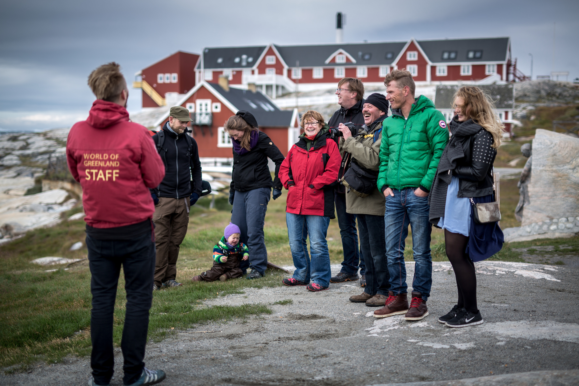 A tour guide entertaining guests on a town walk in Ilulissat in Greenland. By Mads Pihl