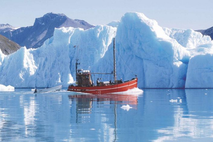 Saling vessel between icebergs in Greenland. Photo by Blue Ice Explorer, Visit Greenland.