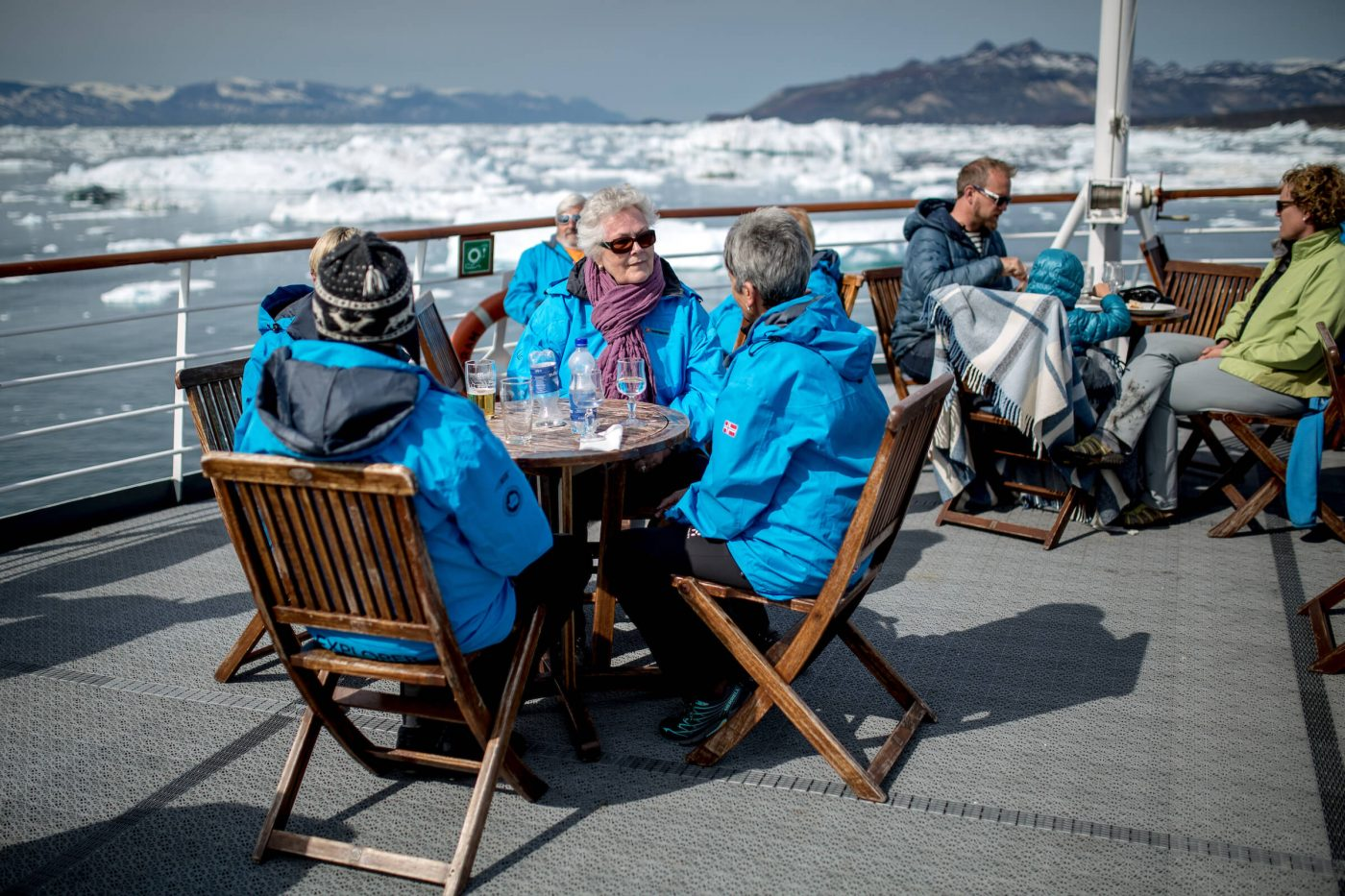 Cruise guests having lunch on the upper deck of MS Fram in the Disko Bay in Greenland. Photo by Mads Pihl