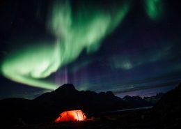 Northern lights over a lit tent, Camp In Tasiilaq Fjord. Photo by Chris Brinlee J