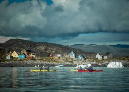 PGI Greenland kayakers paddling past Oqaatsut in the Disko Bay in Greenland. By Mads Pihl