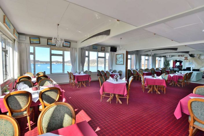 Inside view of the restaurant with a view of Ilulissat Icefjord in the background. Photo by Restaurant Hvide Falk