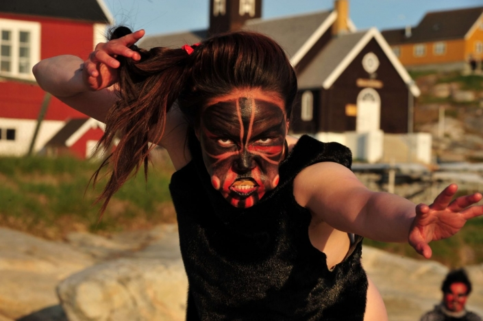 Woman mask dancing on a sunny day in Aasiaat. Photo by Honest Greenland - Visit Greenland