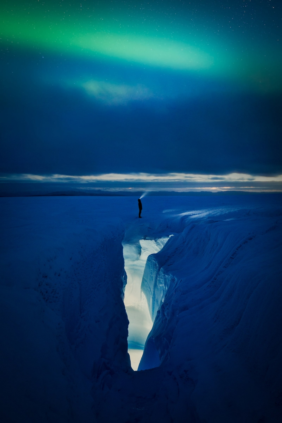 A man with a flash light looking up to the northern lights by a crevasse on the Greeland Ice Sheet near Kangerlussuaq. Photo by Paul Zizka - Visit Greenland