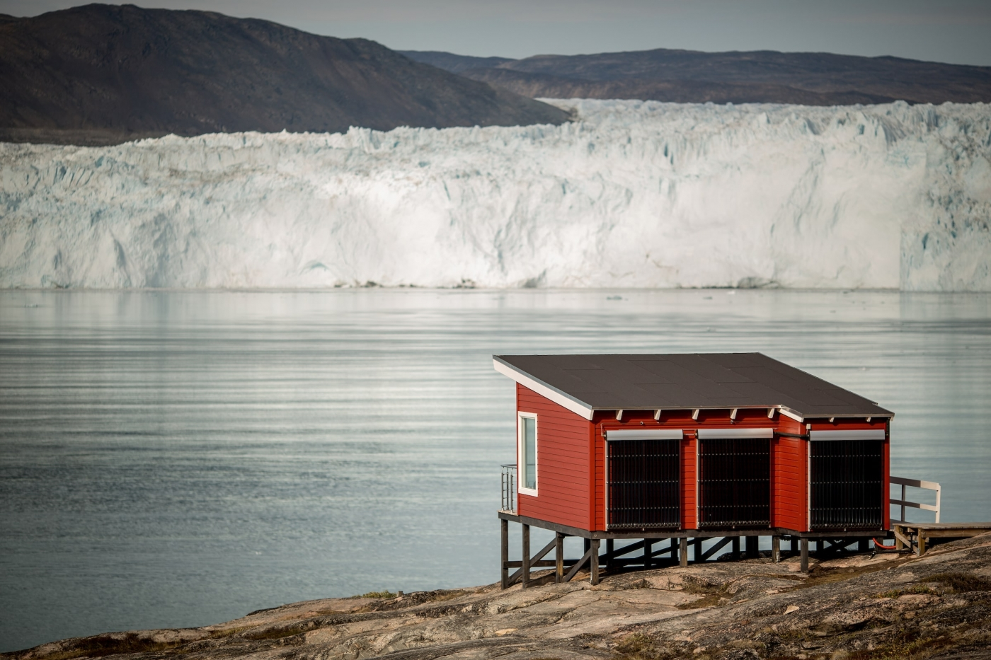 A comfort hut at Eqi Glacier Lodge with the glacier in the background in North Greenland. Photo by Mads Pihl - Visit Greenland