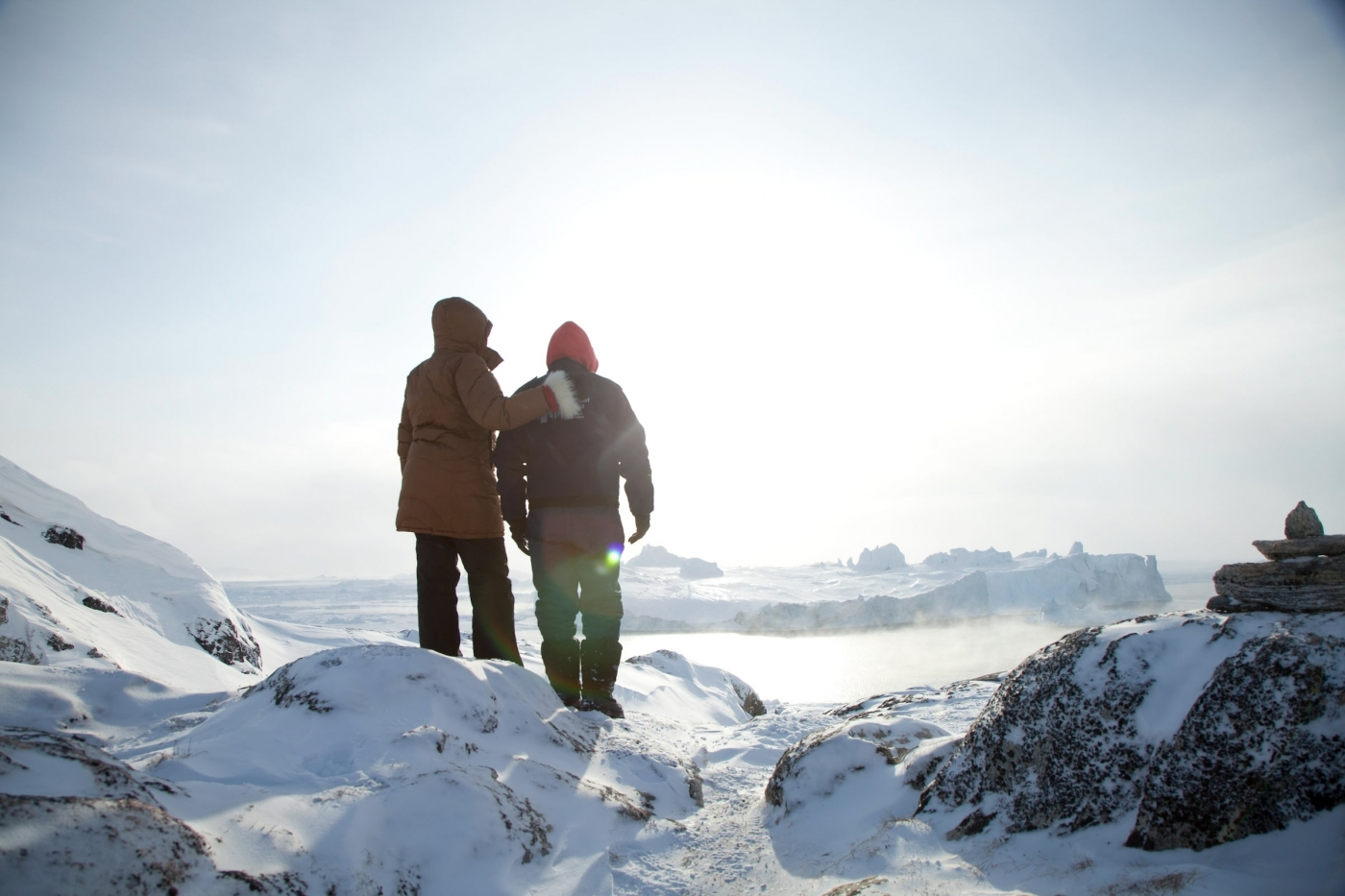 A couple of travelers overlooking an iceberg on a crisp winter's day near Ilulissat Ice Fjord in Greenland. Photo by David Trood - Visit Greenland