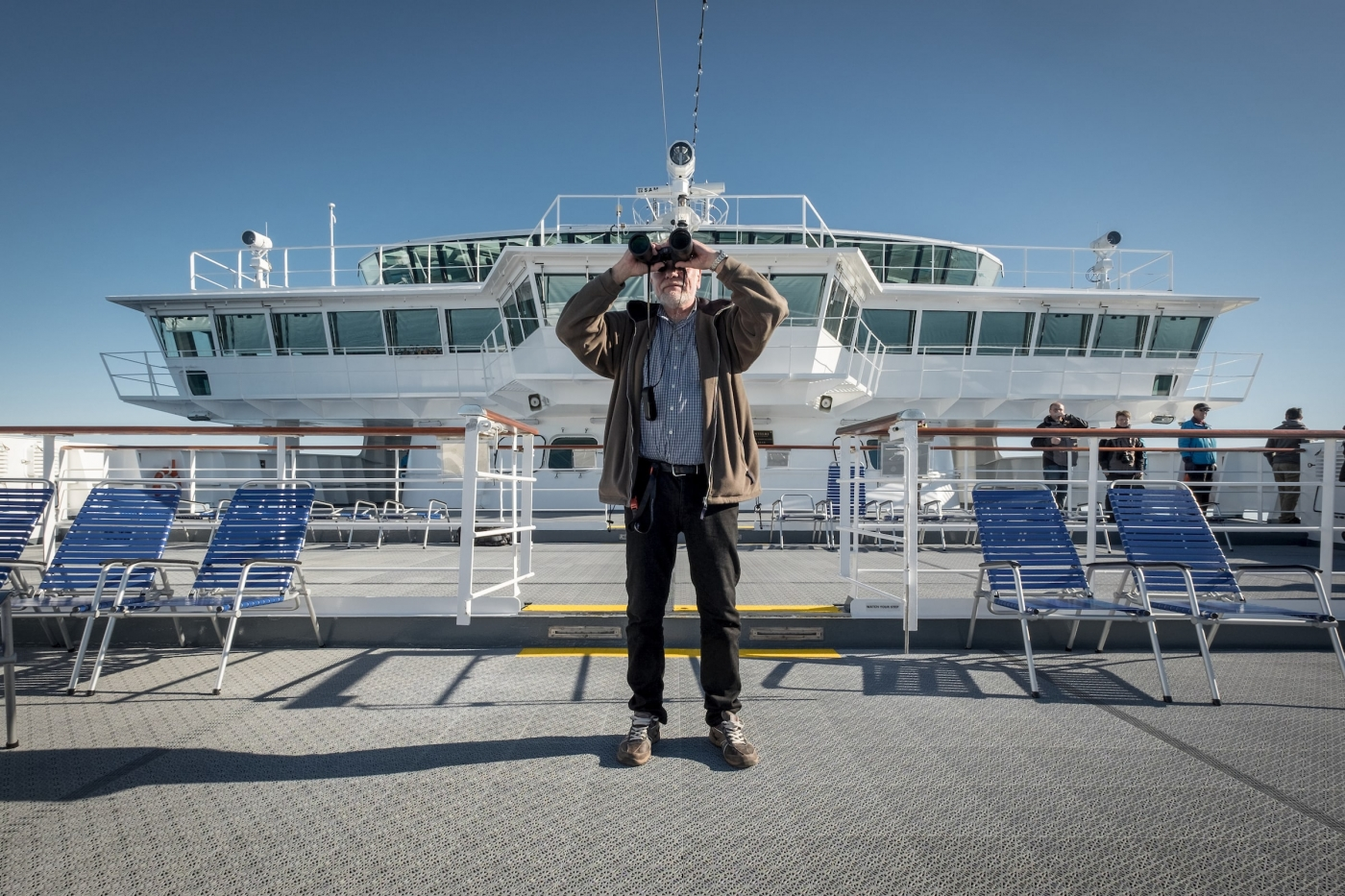 A cruise guest with binoculars on the deck of MS Fram in Greenland. By Mads Pihl