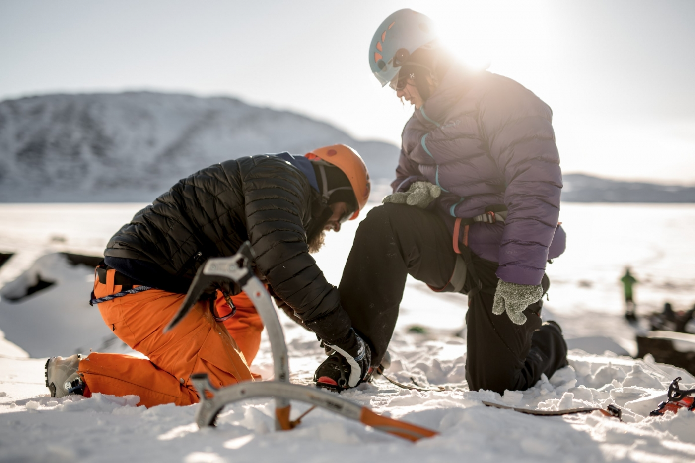 A guide helping a guest getting ready to go ice climbing in Greenland. Photo by Mads Pihl - Visit Greenland