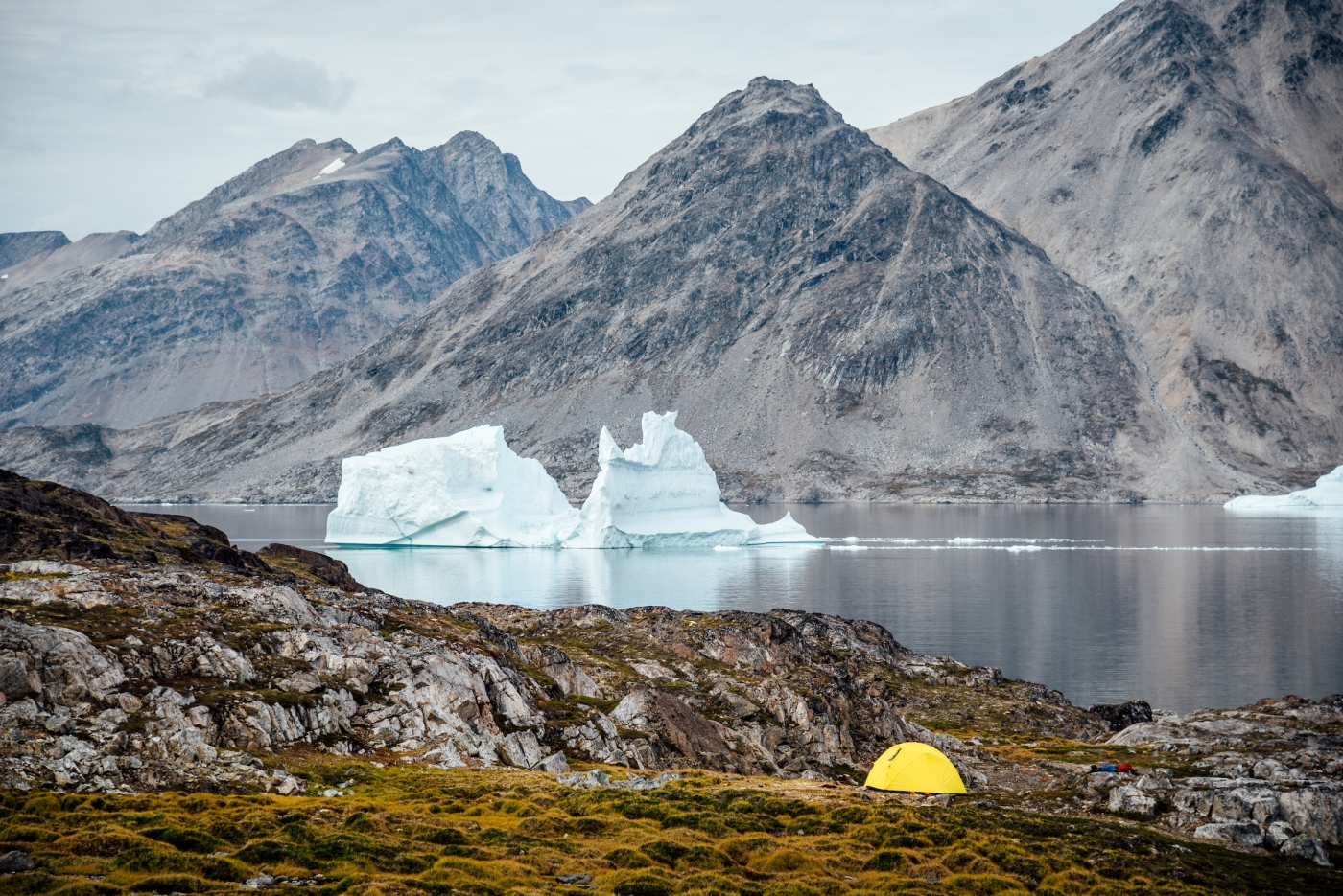 A tent site with an iceberg in the background, Between Kulusuk & Kuummiut.Photo by Chris Brin Lee Jr. - Visit Greenland