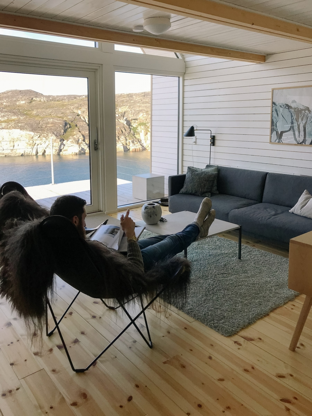 A tourist relaxes and reads inside the Iliminaq Lodge. Photo by Jessie Brinkman Evans - Visit Greenland