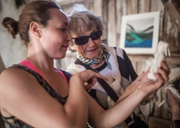 Kattie from Hotel Narsaq telling a guest about a tupilak bone carving from Narsaq in South Greenland. Photo by Mads Pihl - Visit Greenland