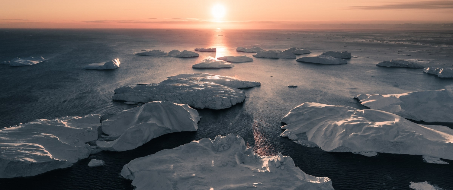 The sun perfectly aligned with the ice bergs that evening. Photo by Ben Simon Rehn - Visit Greenland
