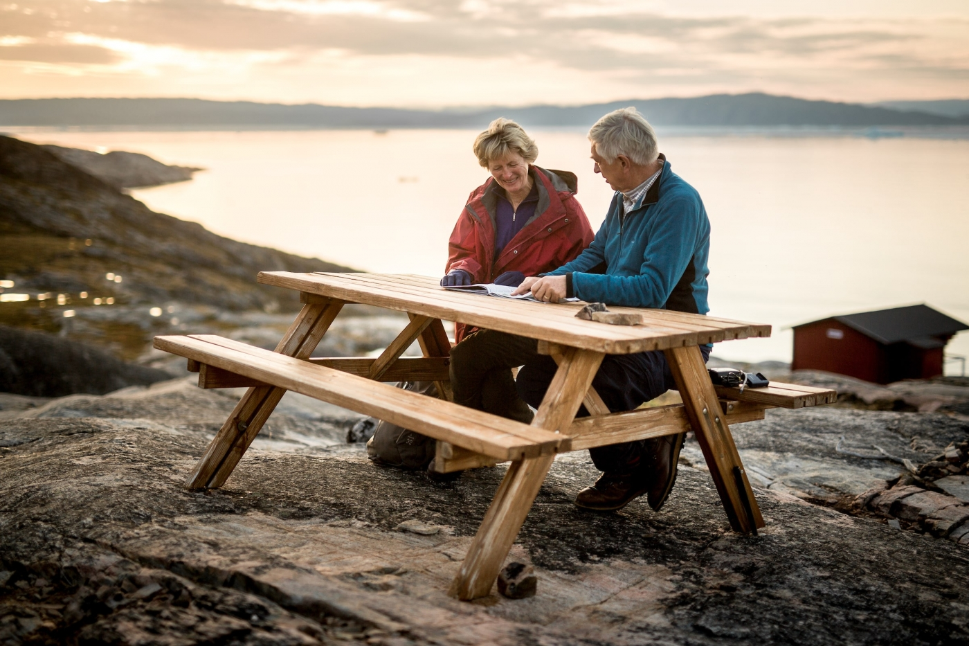 Two guests at Eqi Glacier Lodge in Greenland studying a map in the sunset. By Mads Pihl