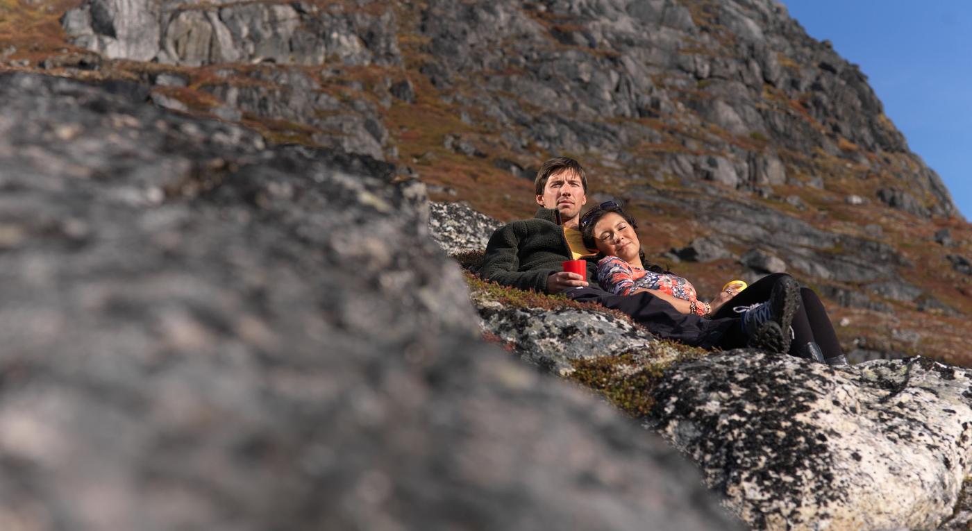 Two hikers on a mountain side enjoying the sun near Nuuk in Greenland. Photo by David Trood - Visit Greenland