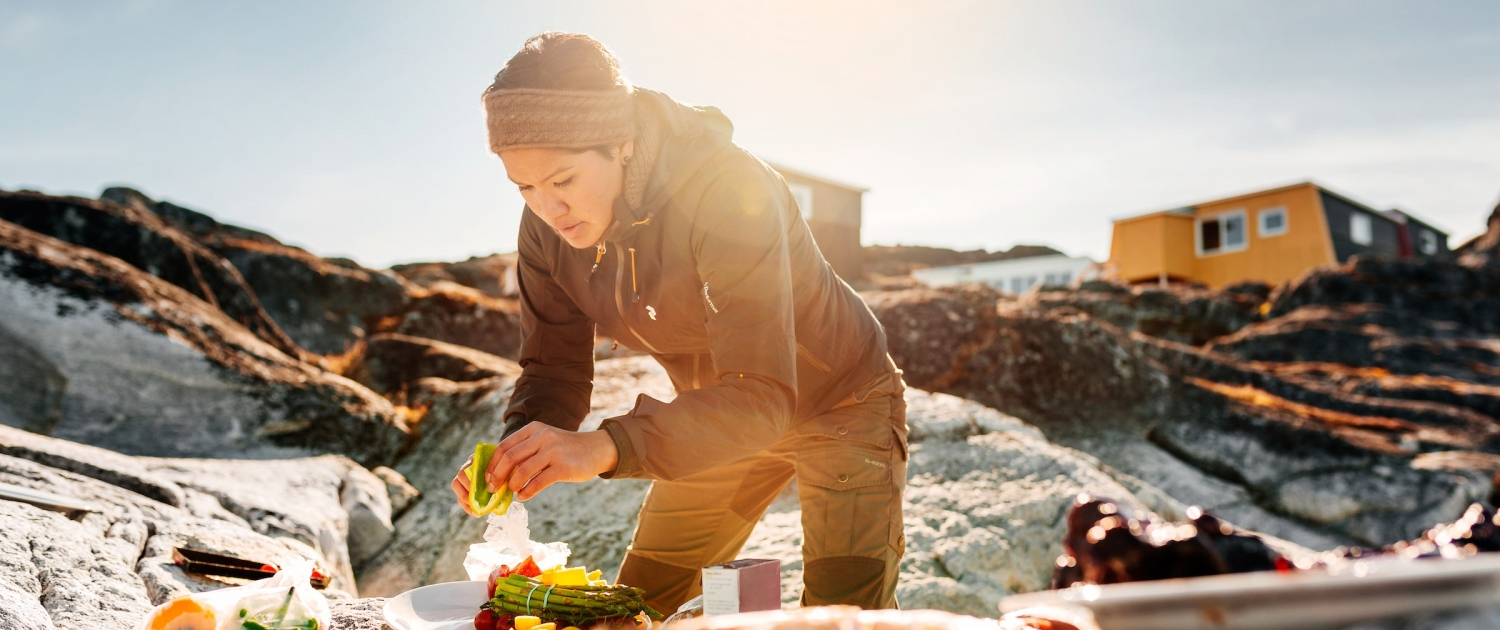 Woman preparing greenladic specialties on the rocks on the beach by Inuk Hostels in Nuuk in Greenland. Photo by Rebecca Gustafsson - Visit Greenland