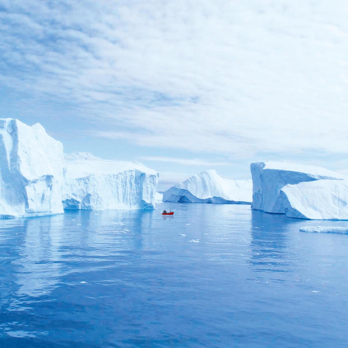 A boat near Aasiaat inbetween large icebergs.