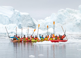kajakgruppe-med-pagajer-i-luften-foran-isbjerg-photo-by-david-d-grant