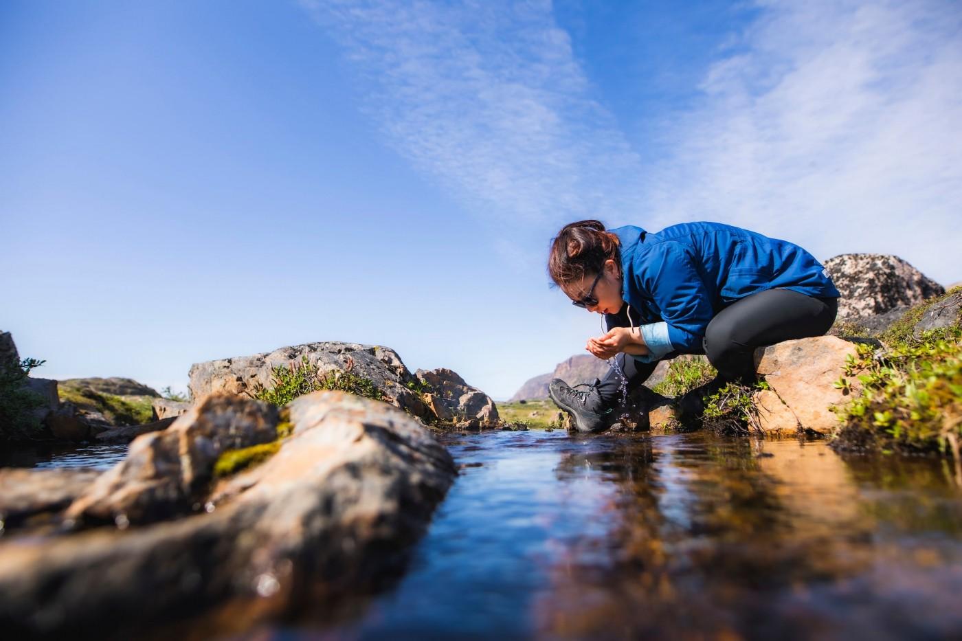Hiker drinking fresh water from stream. Photo-Aningaaq Rosing Carlsen - Visit Greenland