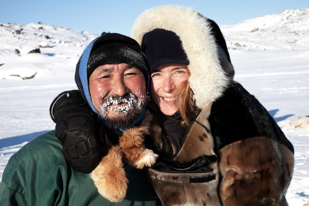 A dog sled driver and his happy passenger enjoying a day of dog sledding in Ilulissat in Greenland