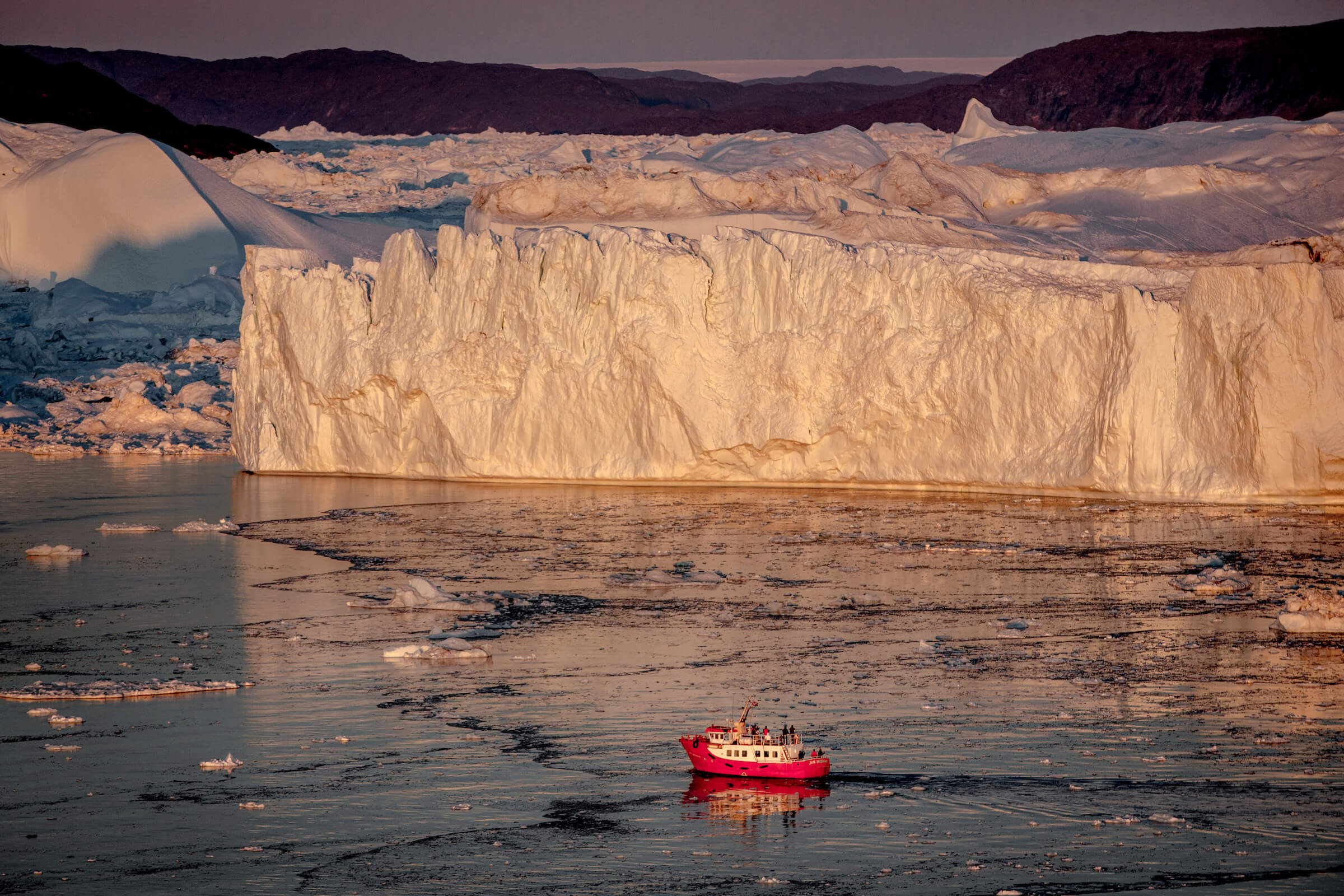 A passenger boat in the sunset near the icebergs of Ilulissat ice fjord in Greenland. By Mads Pihl