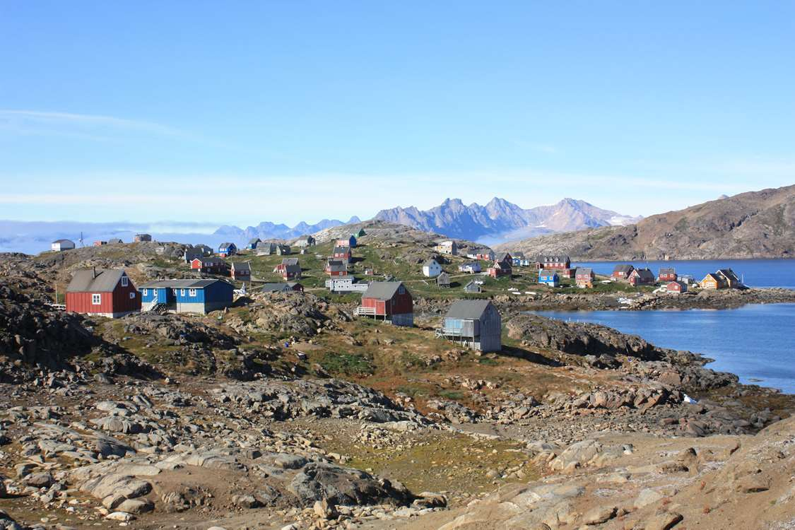View of greenlandic city by the coast with mountains in the background.