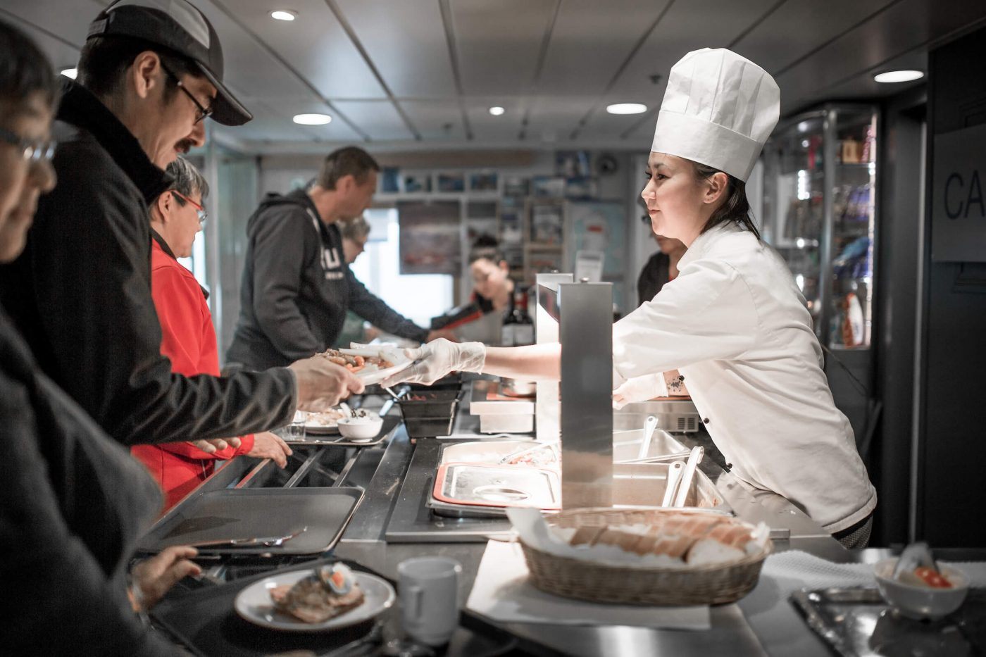 A chef serving dinner on board the passenger ferry Sarfaq Ittuk in Greenland