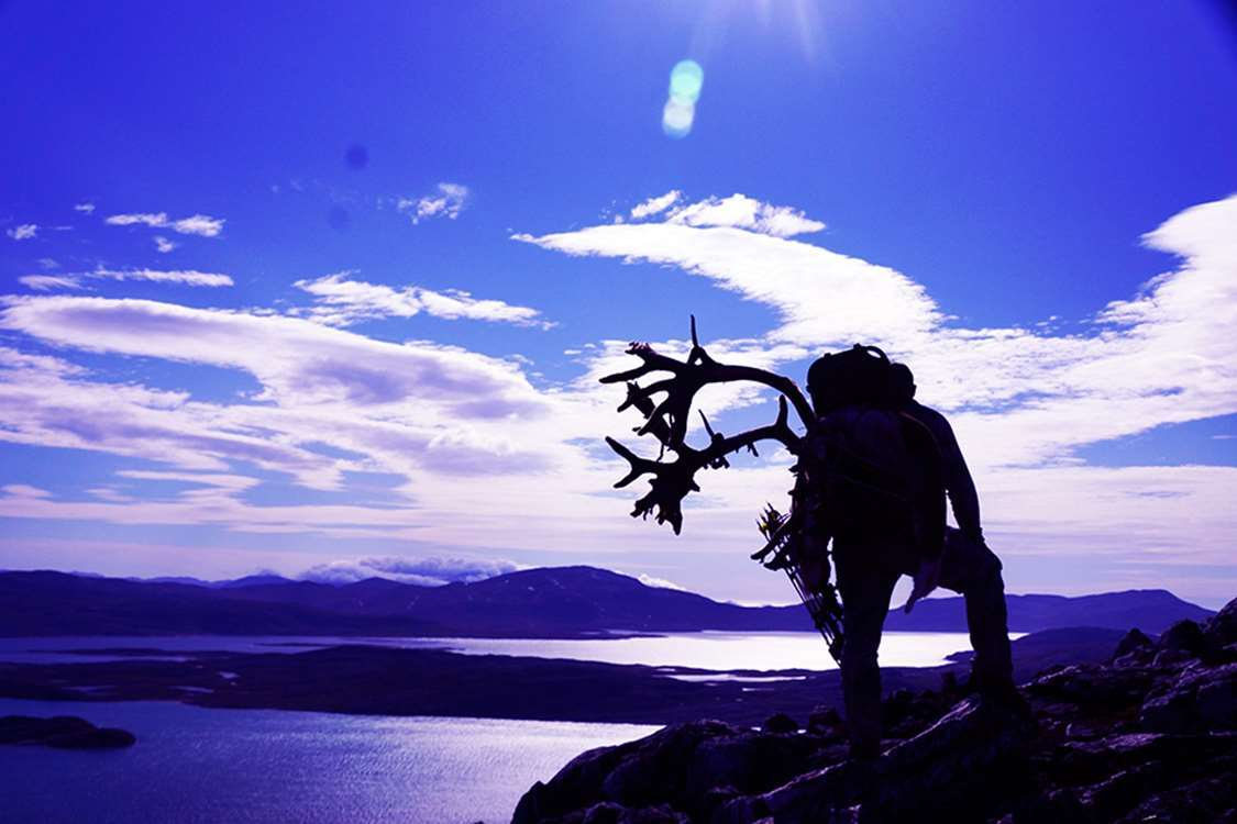 Purple landscape with a silhouette of a man carrying reindeer antlers on his back. Photo by Bowhunting Greenland