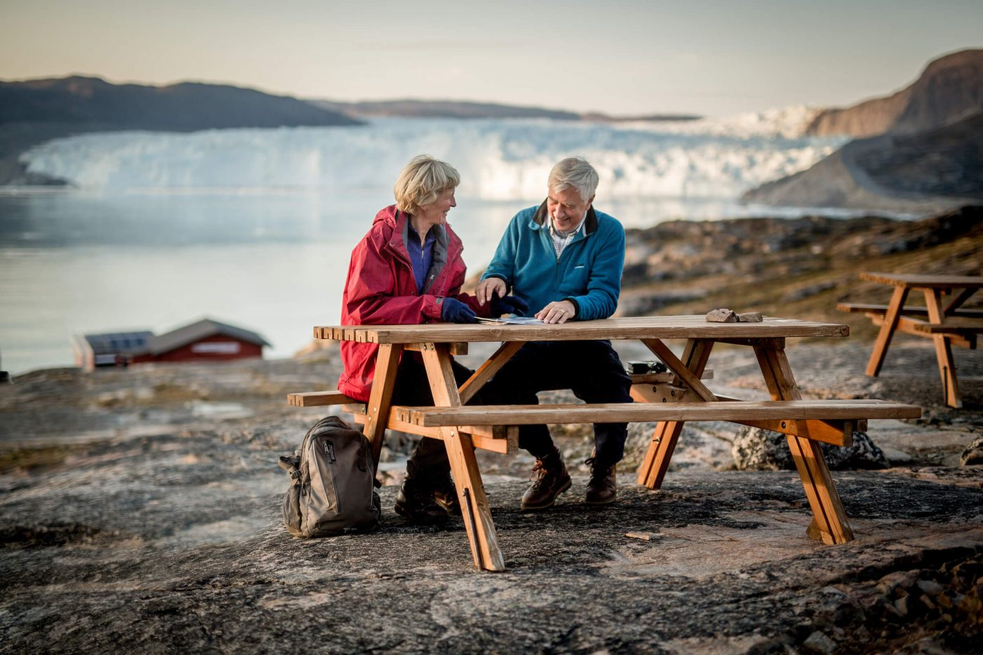 Two guests at Eqi Glacier Lodge in Greenland at a picnic table with the glacier in the background. Photo by Mads Pihl, Visit Greenland