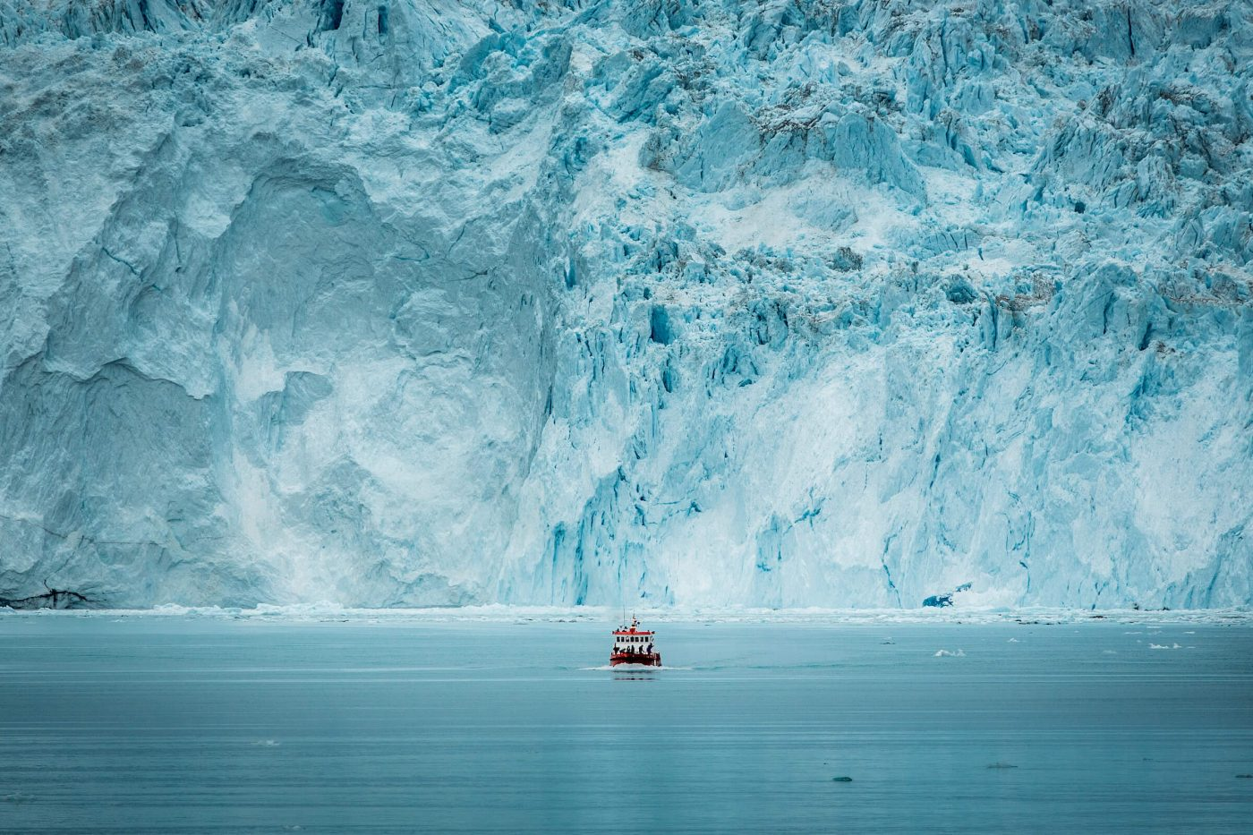 A small passenger boat in front of the huge glacier wall at the Eqi glacier in Greenland. Photo by Mads Pihl