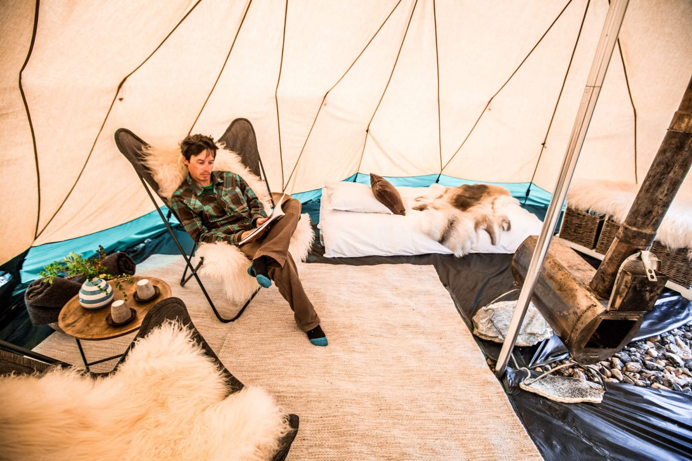 Guest relaxes in luxury with a good book by the fireplace in his private tent at the Arctic Nomad Adventure Camp in Nuuk Fjord. By Raven Eye Photography