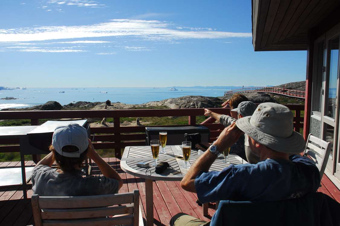 Tourists enjoying a beer on Brasserie Ulos outdoor terrace looking at Ilulisat Icefiord. Photo by Hotel Arctic