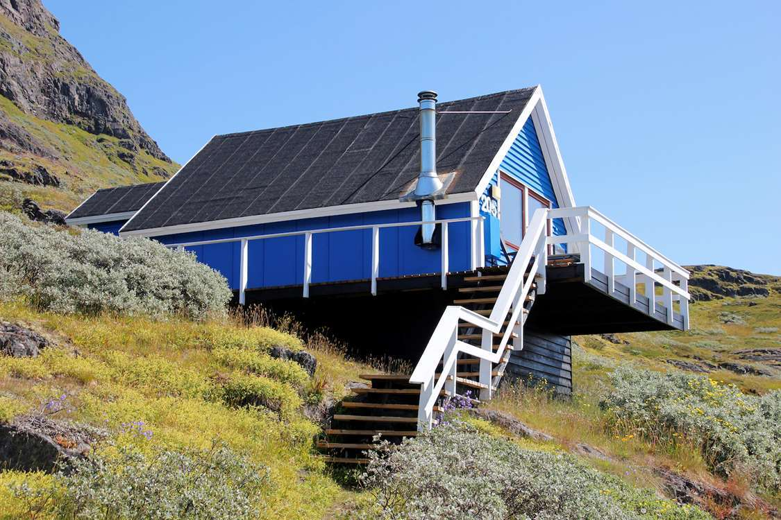 View of small blue wooden house in Summer in Narsaq, South Greenland. Photo by Isikkivik