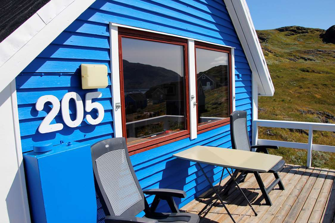 Terrace view of small blue wooden house in Narsaq, South Greenland. Photo by Isikkivik