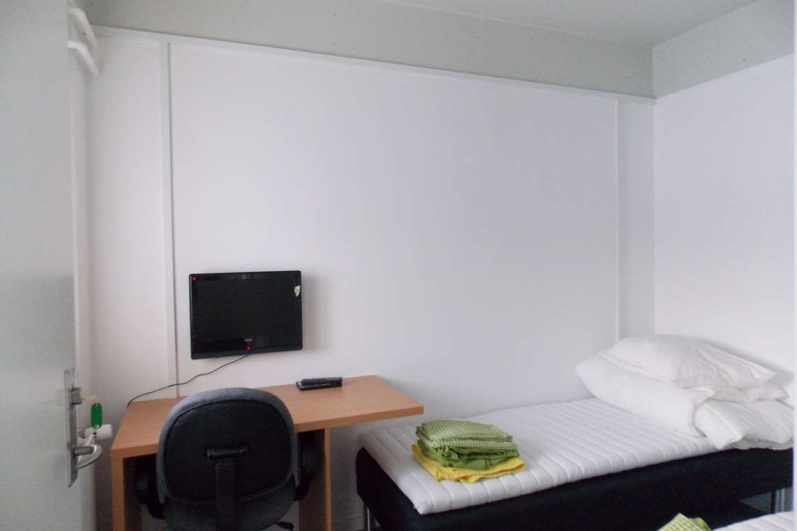 Single bed room with TV and desk. Photo by Kangerlussuaq Youth Hostel - Visit Greenland