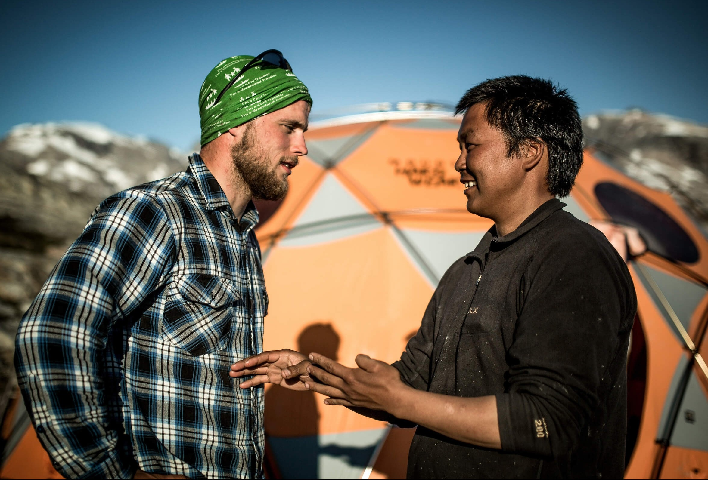 A Greenland Travel hiking guide and a local camp manager from East Greenland discussing the pronounciation of East Greenlandic words. Photo by Mads Pihl, Visit Greenland