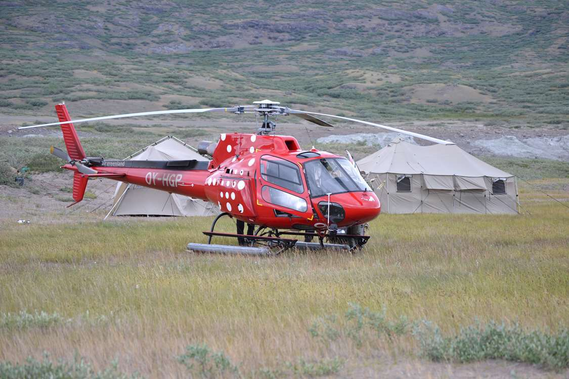 Red Air Greenland helicopter landing in camp field in Summer in Greenland. Photo by Major Hunting