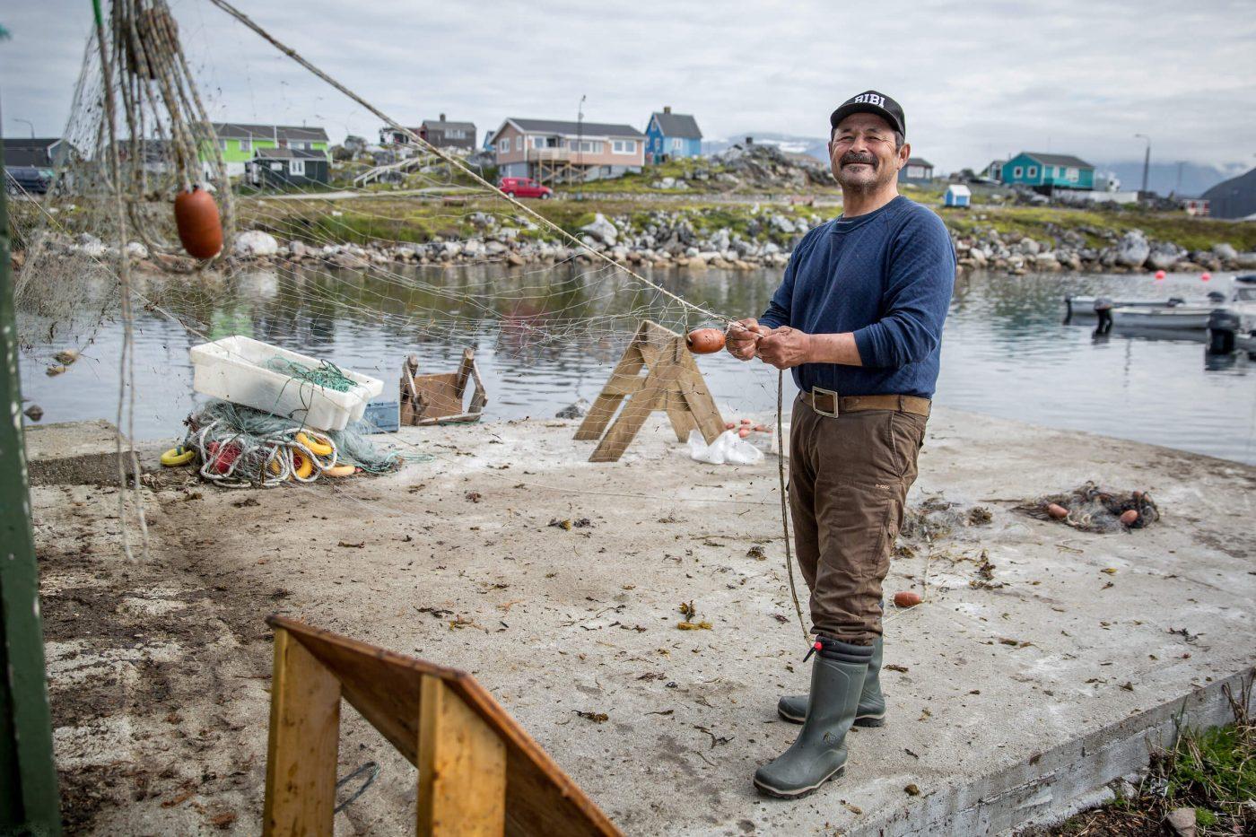 Smiling man with cap preparing his fishing net at the harbour in Nanortalik, South Greenland. Photo by Nanortalik Tourism Service