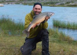 CEO Thomas Olsen of North Safari Outfitters standing with an Arctic char. Photo by North Safari Outfitters