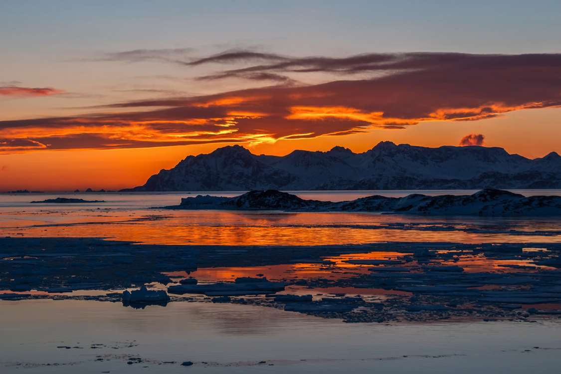 Sunset and small icebergs in East Greenland. Photo by Pirhuk - Greenland Expedition Specialists