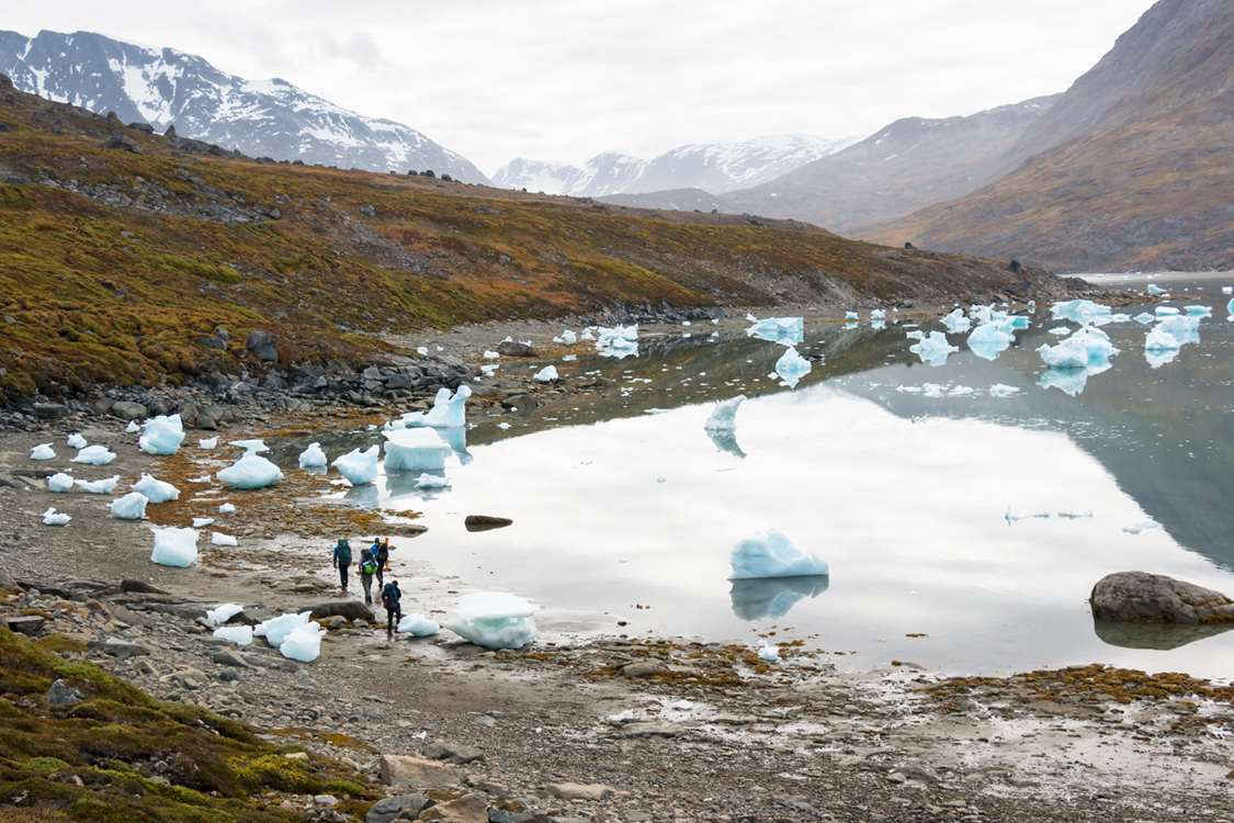 Hiking alongside a beach with icebergs in East Greenland. Photo by Pirhuk - Greenland Expedition Specialists
