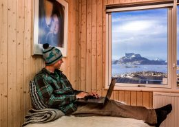 Traveler writes in his adventure log from the comfort of his bed at Inuk Hostels in Nuuk overlooking Nuuk Fjord and Sermitsiaq mountain. By Raven Eye Photography