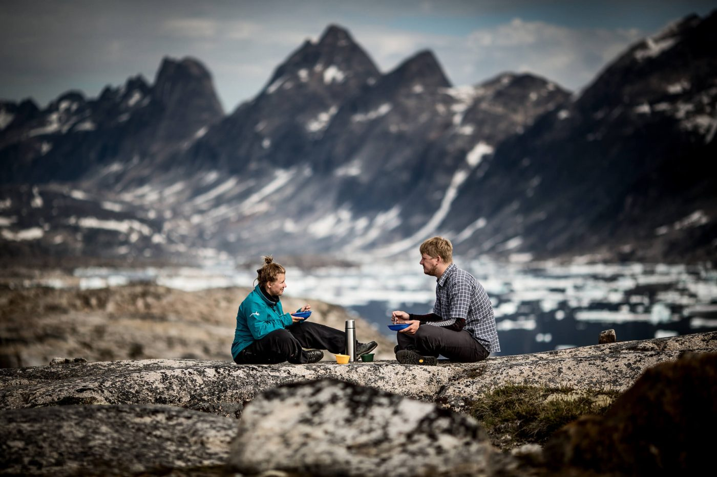 Two hikers having breakfast at a campsite near Qernertivartivit in East Greenland. By Mads Pihl